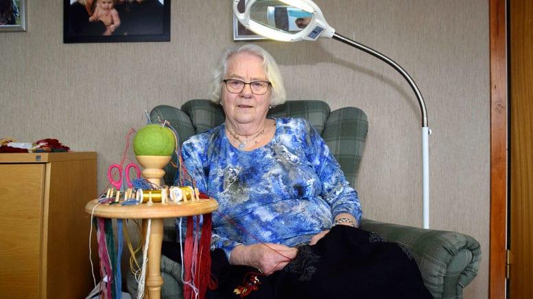 Elsa Selboskar har brukt mange timar i godstolen med broderiet sitt. God hjelp har ho av stativet for broderigarn og nåler som Einar Waldal har laga til ho.